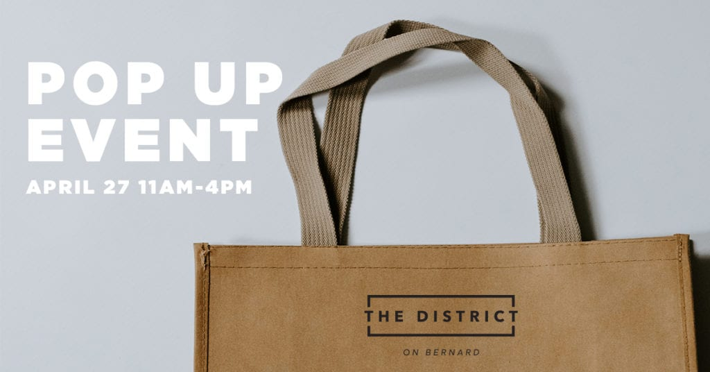 Brown paper bag with The District on Bernard Logo, and text that reads: pop up shop event April 27th 2019