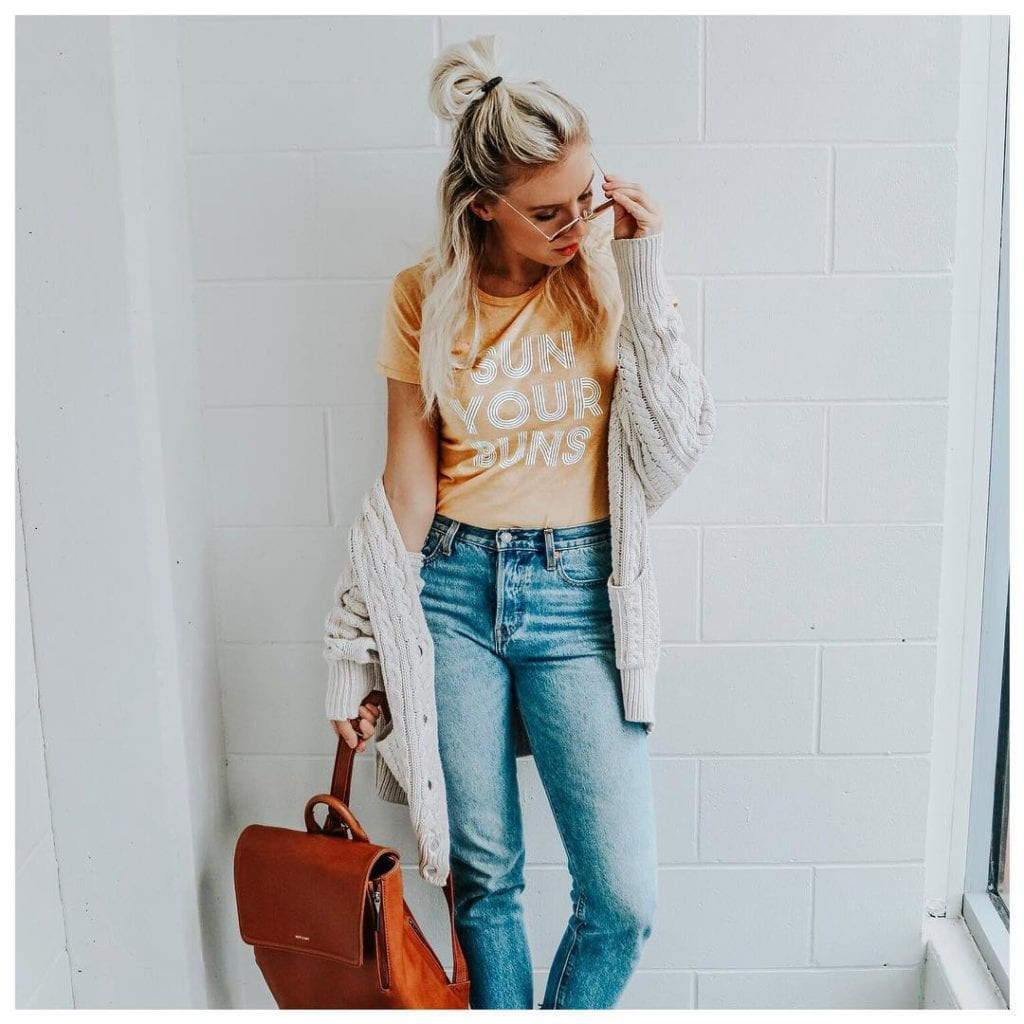 Carly @CarlyMal a fashion blogger from kelowna, here wearing a summer tshirt, jeans, and cardigan with sunglasses and a leather bag