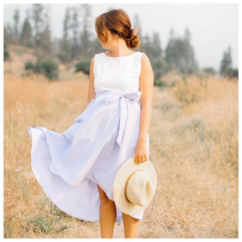 Jillian Harris (@Jillian.Harris) is a fashion influencer and TV star from Vancouver, here she is wearing a pale blue sundress with a beige hat in a Kelowna field with trees behind