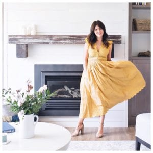 Jillian Harris (@Jillian.Harris) is a fashion influencer and TV star from Vancouver, here she is wearing a bright yellow sundress standing in front of a while brick fireplace in a modern interior