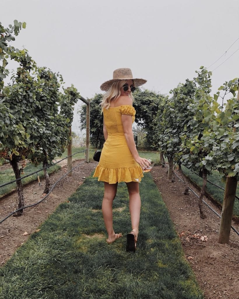 Tessa (@tessalindsaygarcia) is a fashion blogger from Vancouver that frequents the Okanagan; here she wearing a yellow sundress and a beige hat, standing in an orchard